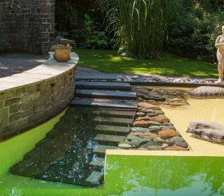 Naturpool mit Treppe und Steinmauer